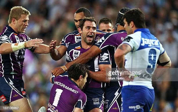 Cameron Smith of the Storm congratulates team mate Billy Slater after he scored a try during the 2012 NRL Grand Final match between the Melbourne...