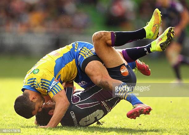 Cameron Smith of the Storm is tackled by Jarryd Hayne of the Eels during the round 15 NRL match between the Melbourne Storm and the Parramatta Eels...