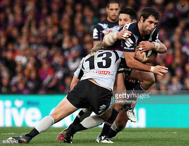 Cameron Smith of the Storm is tackled by Michael Luck and Steve Price of the Warriors during the fourth NRL qualifying final match between the...
