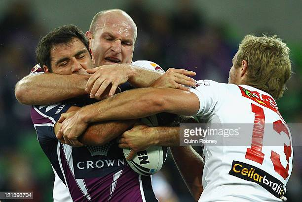 Cameron Smith of the Storm is tackled by Michael Weyman and Matt Prior of the Dragons during the round 24 NRL match between the Melbourne Storm and...