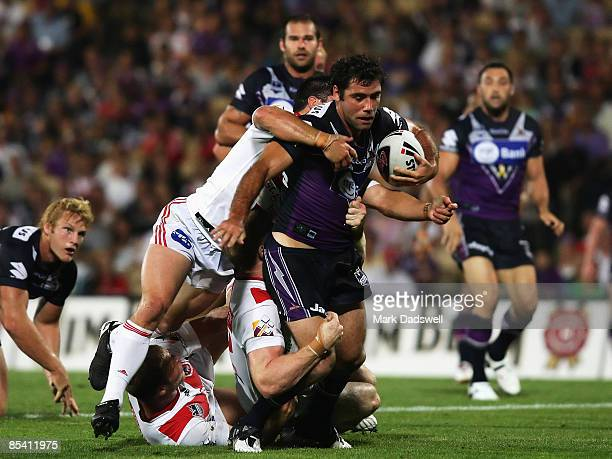 Cameron Smith of the Storm is tackled during the round one NRL match between the Melbourne Storm and the St George Illawarra Dragons at Olympic Park...