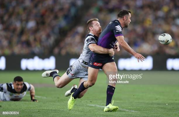 Cameron Smith of the Storm offloads as he is tackled by Michael Morgan of the Cowboys during the 2017 NRL Grand Final match between the Melbourne...