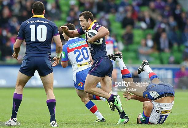 Cameron Smith of the Storm runs with the ball past Robbie Rochow of the Knights during the round 14 NRL match between the Melbourne Storm and the...