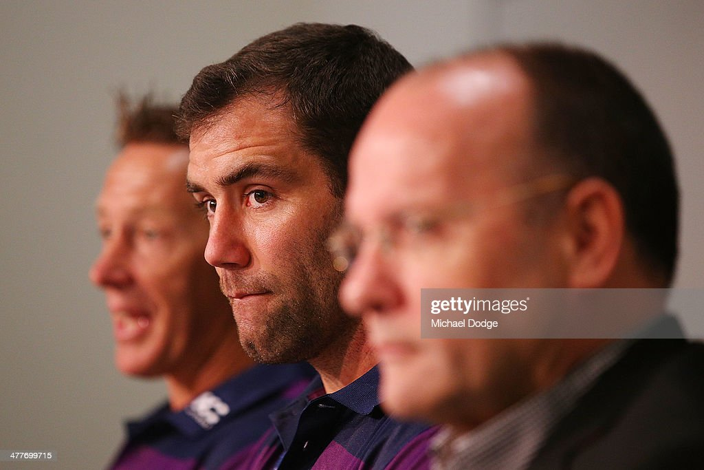 Cameron Smith (C) of the Storm, who has signed a four year contract extension and breaks the game record for a Storm player this weekend, speaks to media with coach Craig Bellamy and CEO Mark Evans (R) aduring a Melbourne Storm NRL media session at AAMI Park on March 11, 2014 in Melbourne, Australia.
