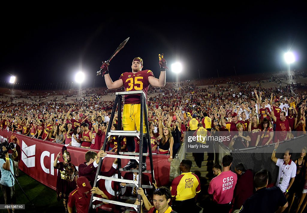 Cameron Smith #35 of the USC Trojans celebrates a 42-24 win over the Utah Utes with fans after his three interception game at Los Angeles Memorial Coliseum on October 24, 2015 in Los Angeles, California.