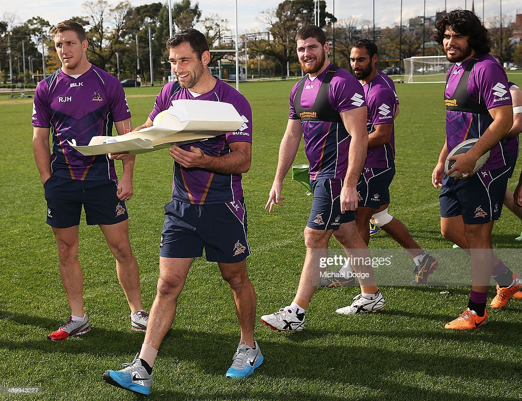 Cameron Smith prepares to present coach Craig Bellamy a cake to celebrate his 300th game as Storm coach during his Melbourne Storm NRL media session at Gosch's Paddock on May 13, 2014 in Melbourne, Australia.