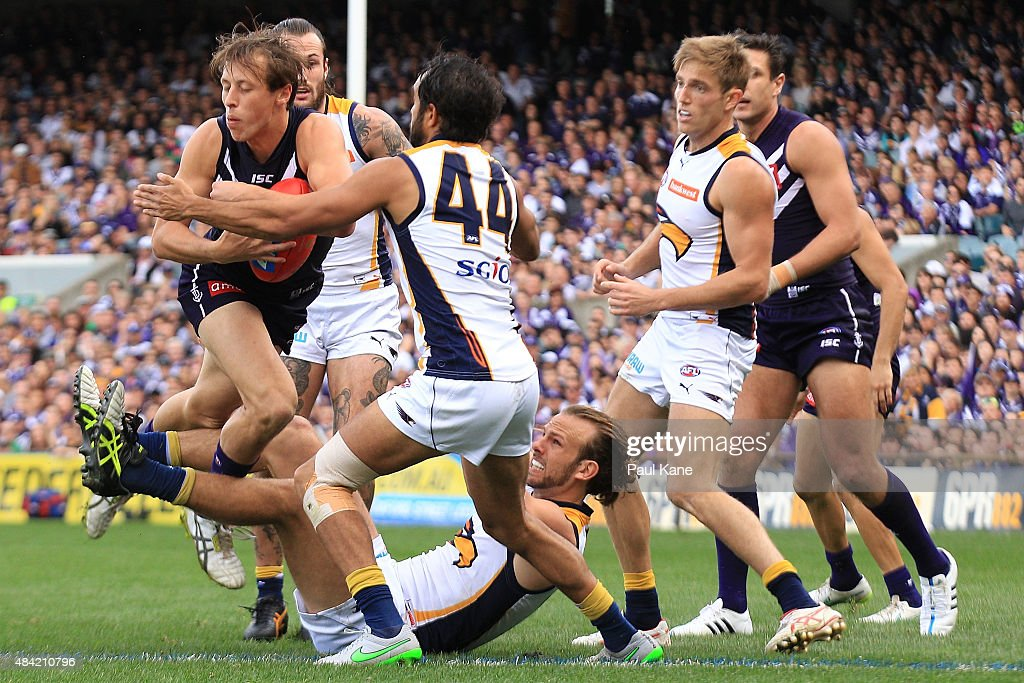 Cameron Sutcliffe of the Dockers gets tackled by Will Schofield and Jamie Bennell of the Eagles during the round 20 AFL match between the Fremantle Dockers and the West Coast Eagles at Domain Stadium on August 16, 2015 in Perth, Australia.