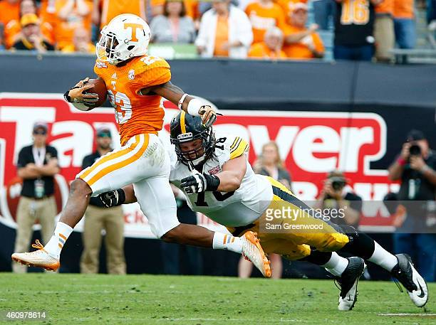 Cameron Sutton of the Tennessee Volunteers runs past Dalton Ferguson of the Iowa Hawkeyes during the TaxSlayer Bowl at EverBank Field on January 2...