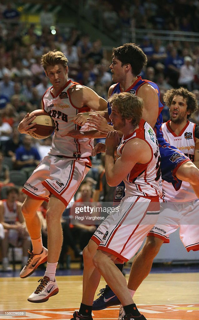 Cameron Tovey of the Wildcats tries to keep the ball in play while being challenged by Stephen Weigh of the 36ers during the round six NBL match between the Adelaide 36ers and the Perth Wildcats at Adelaide Arena on November 11, 2012 in Adelaide, Australia.