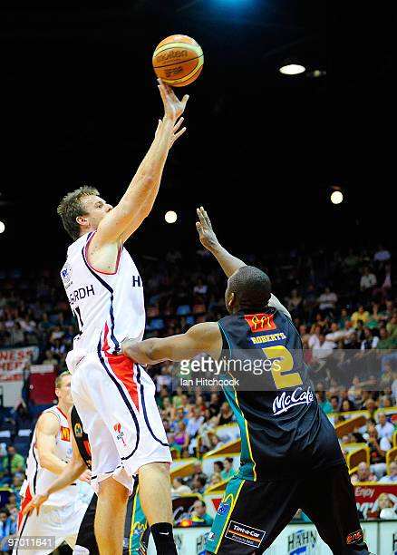Cameron Tragardh of the Hawks makes a jump shot over Rolan Roberts of the Crocodiles during game two of the NBL semi final series between the...