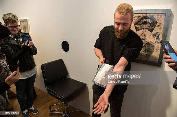 Cameron Ward unveils his first ever tattoo done through a hole in the wall at celebrity tattoo artist Scott Campbell's event 'Whole Glory' on October...