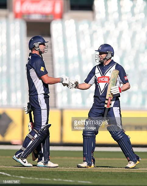 Cameron White and David Hussey of Bushrangers celebrate their century partnership during the Ryobi One Day Cup match between Victorian Bushrangers...