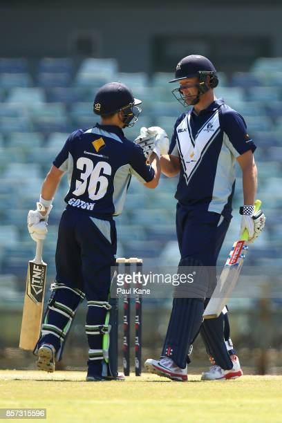 Cameron White of the Bushrangers celebrates his century with Seb Gotch during the JLT One Day Cup match between Victoria and Tasmania at WACA on...