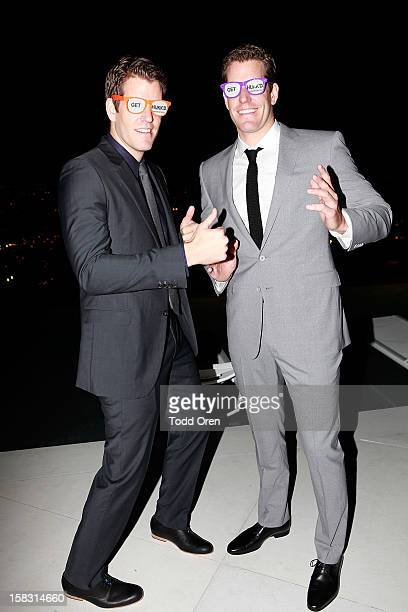 Cameron Winklevoss and Tyler Winklevoss pose at the Hukkster Holiday Party at a Private Residence on December 12 2012 in Los Angeles California