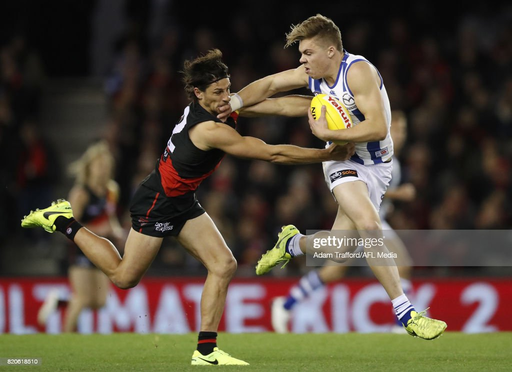 Cameron Zurhaar of the Kangaroos fends off Mark Baguley of the Bombers during the 2017 AFL round 18 match between the Essendon Bombers and the North Melbourne Kangaroos at Etihad Stadium on July 22, 2017 in Melbourne, Australia.