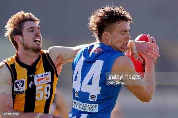 Cameron Zurhaar of the Kangaroos marks the ball under the defensive pressure of Kaiden Brand of the Hawks during the round eight VFL match between...