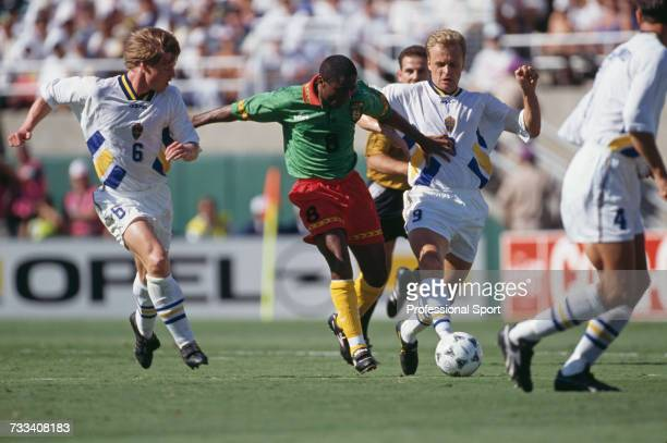Cameroon footballer Emile Mbouh advances with the ball through a gap between Swedish players Stefan Schwarz on left and Jonas Thern on right during...