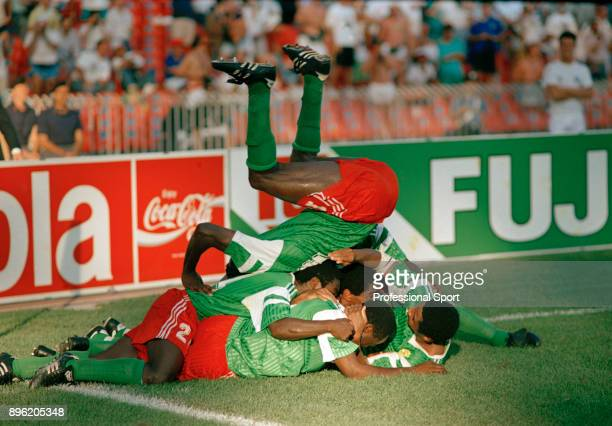 Cameroon players pile on top of each other as they celebrate the winning goal scored by Roger Milla during the 1990 FIFA World Cup 2nd Round match...