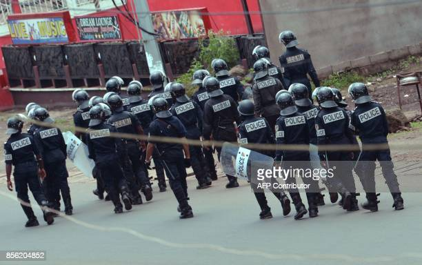 Cameroon police officers walk with riot shields on a street in the administrative quarter of Buea some 60kms west of Douala on October 1 2017 A young...