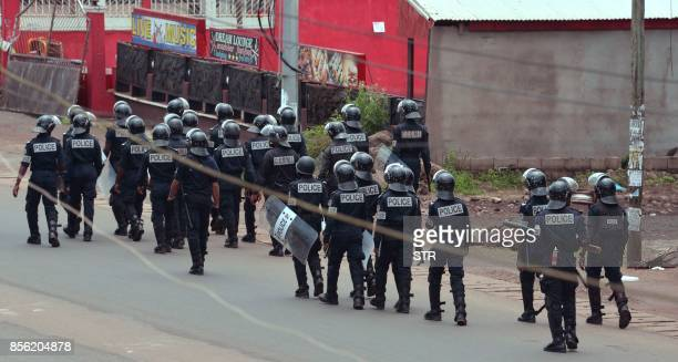 Cameroon police officials walk with riot shields on a street in the administrative quarter of Buea some 60kms west of Douala on October 1 2017 A...