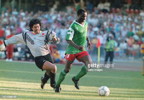 Cameroon striker Roger Milla walks the ball into the empty net to score the winning goal after dispossesing Colombian goalkeeper Rene Higuita of the...