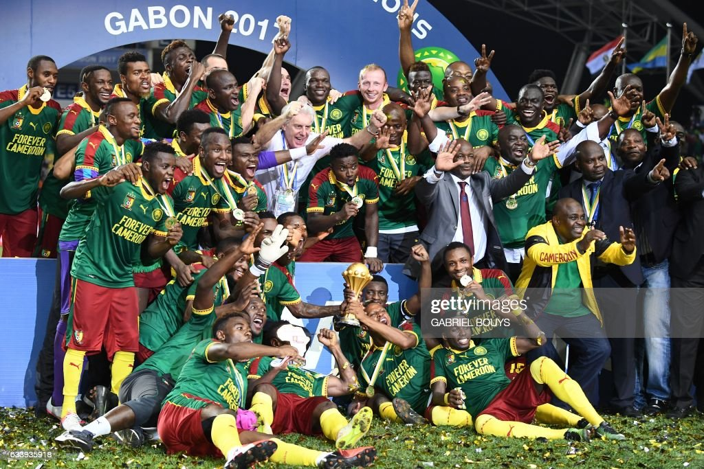 TOPSHOT - Cameroon team players and Cameroon's Belgian coach Hugo Broos (C) celebrate after beating Egypt 2-1 to win the 2017 Africa Cup of Nations final football match between Egypt and Cameroon at the Stade de l'Amitie Sino-Gabonaise in Libreville on February 5, 2017. /