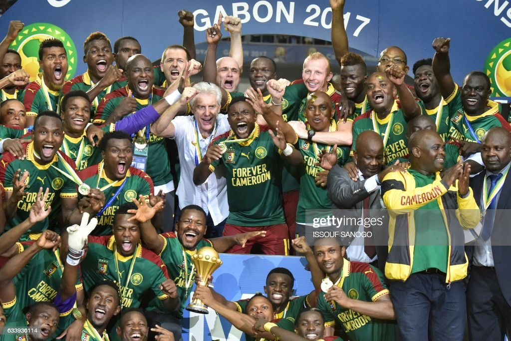 TOPSHOT - Cameroon team players and Cameroon's Belgian coach Hugo Broos (C) celebrate with the winner's trophy after beating Egypt 2-1 to win the 2017 Africa Cup of Nations final football match between Egypt and Cameroon at the Stade de l'Amitie Sino-Gabonaise in Libreville on February 5, 2017. /