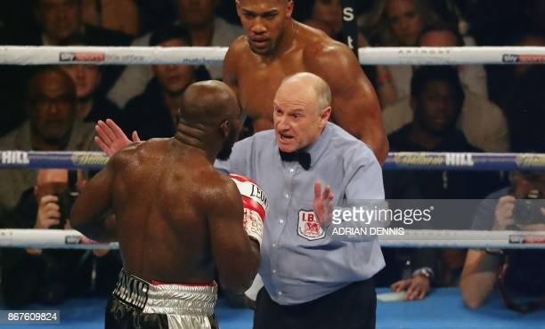 Cameroonborn Carlos Takam complains to referee Phil Edwards after being cut in the fourth round against Britain's Anthony Joshua during their world...