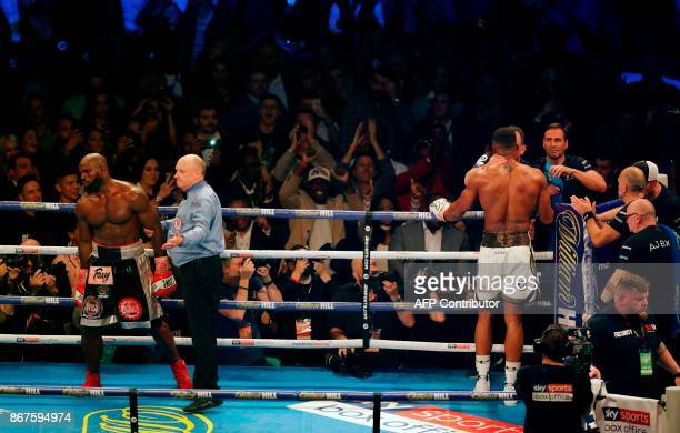 Cameroonborn Carlos Takam reacts as referee Phil Edwards stops the fight against Britain's Anthony Joshua during their world Heavyweight title fight...