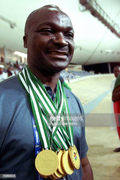 Cameroonian football legend Roger Milla smiles at the Abuja Stadium Velodrome 13 October 2003 after being decorated with 12 medals won by members of...