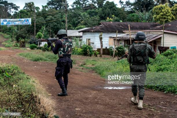 A Cameroonian policeman and a gendarme aim their weapons while securing the perimeter of a polling station in Lysoka near Buea southwestern Cameroon...