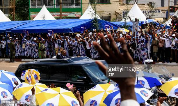 Cameroonian President Paul Biya waves to supporters from his motorcade as he celebrates his re-election in Yaoundé on November 6, 2018. - Cameroon's...
