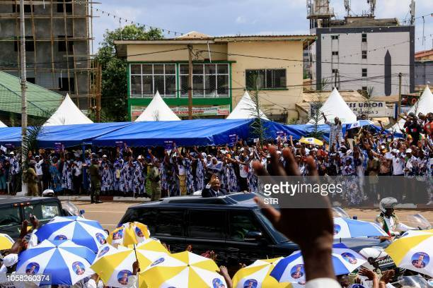 Cameroonian President Paul Biya waves to supporters from his motorcade as he celebrates his reelection in Yaoundé on November 6 2018 Cameroon's...