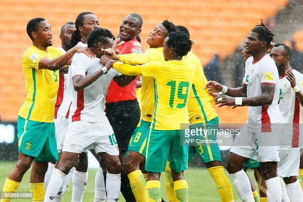TOPSHOT Cameroonian referee Alioum Neant attempts to separate South Africa's Bongani Zungu and Burkina Faso's Alain Traore scuffling during the Fifa...