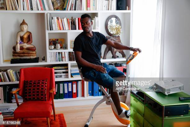 Cameroonian refugee Emilien Atanga sits on an apartment bike in a flat he rent for free for the past three months through AirBnB on July 18 2017 in...