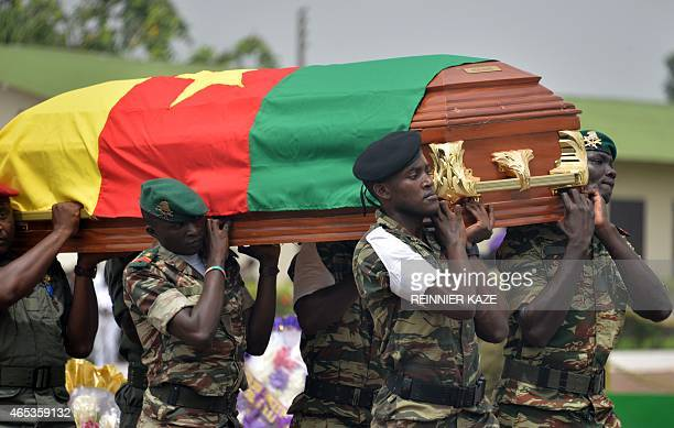 Cameroonian soldiers carry a coffin covered with Cameroonian flags containing the remains of a fellow soldier during a ceremony for 38 soldiers who...