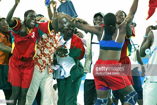 Cameroonian supporters jubilate as a member of the handball team pulls off her tops to celebrate their victory over Ivory Coast, 13 October 2003 at...