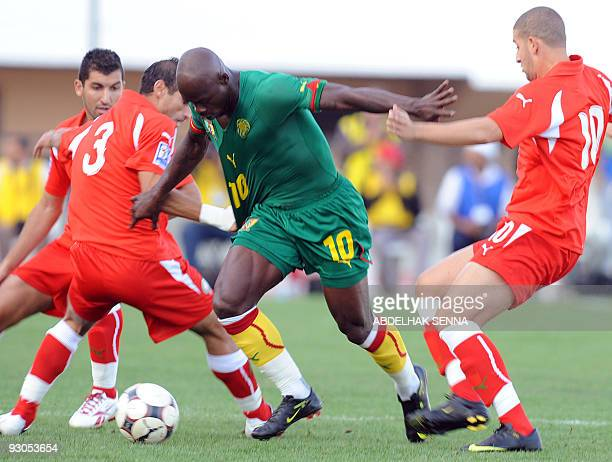 Cameroon's Achille Emana fights for the ball with Morocco's Zakaria Zerouali and Adel Taarabt during their Fifa 2010 World Cup play off match on...