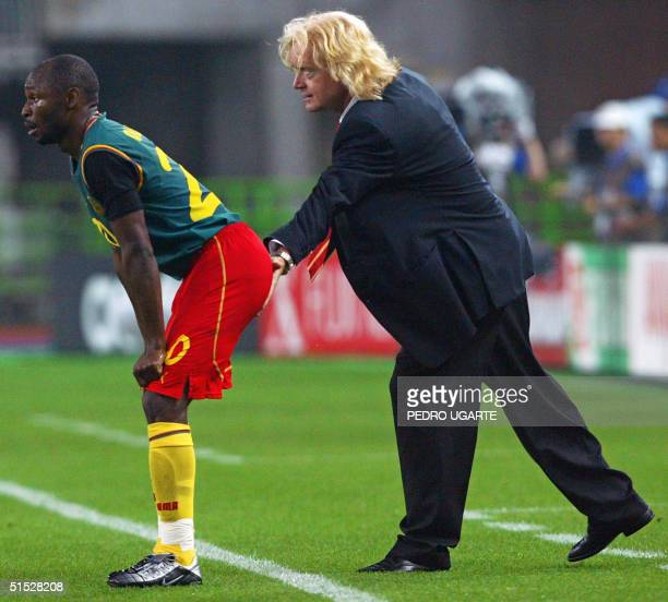 Cameroon's coach Winnie Schaefer from Germany taps Cameroon's defender Salomon Olembe on the buttocks during match 35 group E of the 2002 FIFA World...