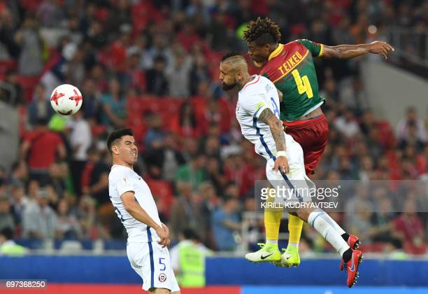TOPSHOT Cameroon's defender Adolphe Teikeu heads the ball with Chile's midfielder Arturo Vidal next to Chile's midfielder Francisco Silva during the...