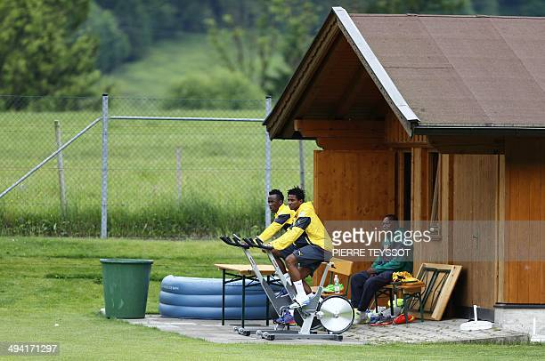 Cameroon's defender Cedric Djeugoue and Cameroon's forward Fabrice Olinga attend a training session in Walchsee Austria on May 28 2014 ahead of a...