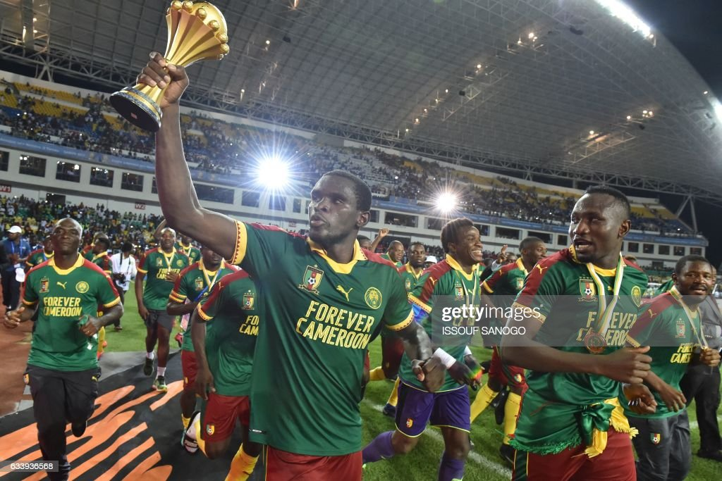 TOPSHOT - Cameroon's defender Michael Ngadeu-Ngadjui holds up the trophy as the team celebrates beating Egypt 2-1 to win the 2017 Africa Cup of Nations final football match between Egypt and Cameroon at the Stade de l'Amitie Sino-Gabonaise in Libreville on February 5, 2017. /