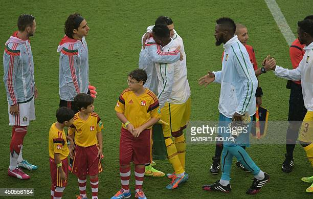 Cameroon's forward and captain Samuel Eto'o hugs Mexico's defender and captain Rafael Marquez before the start of a Group A football match between...