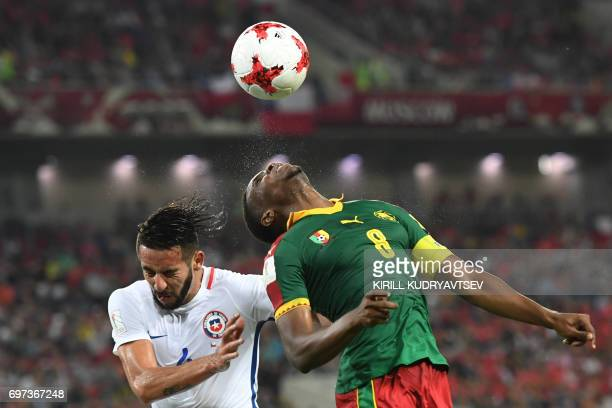 Cameroon's forward Benjamin Moukandjo heads the ball with Chile's defender Mauricio Isla during the 2017 Confederations Cup group B football match...