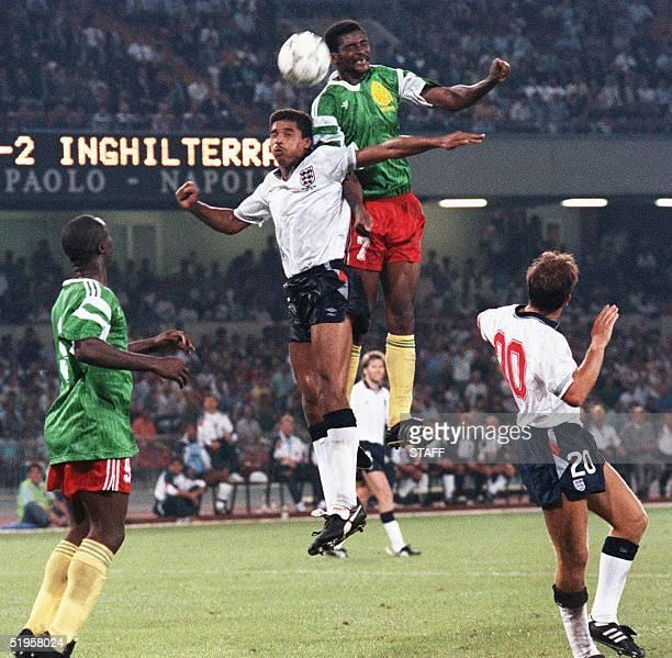 Cameroon's forward Frantois Omam Biyick heads the ball over English defender Des Walker as forward Roger Milla and midfielder Trevor Steven look on...