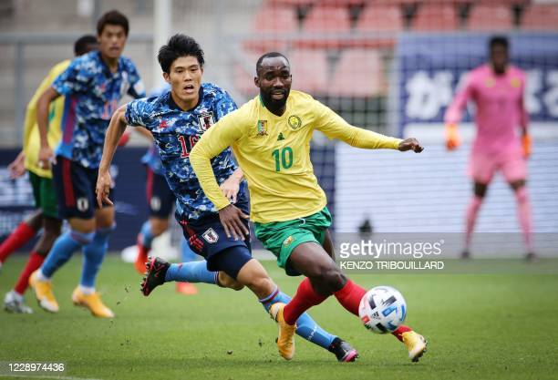 Cameroon's forward Moumi Ngamaleu vies with Japan's defender Takehiro Tomiyasu during a friendly football match between Japan and Cameroon at Stadion...