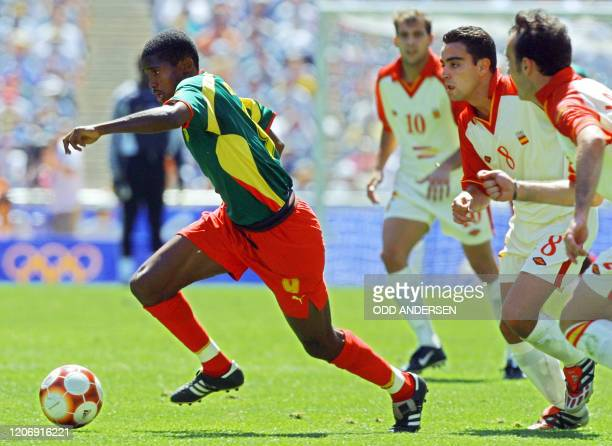 Cameroon's forward Samuel Eto'o Fils runs with the ball to score the 2nd goal of his team as Spain's defenders Gabri, Xavi and Lacruz look on 30...