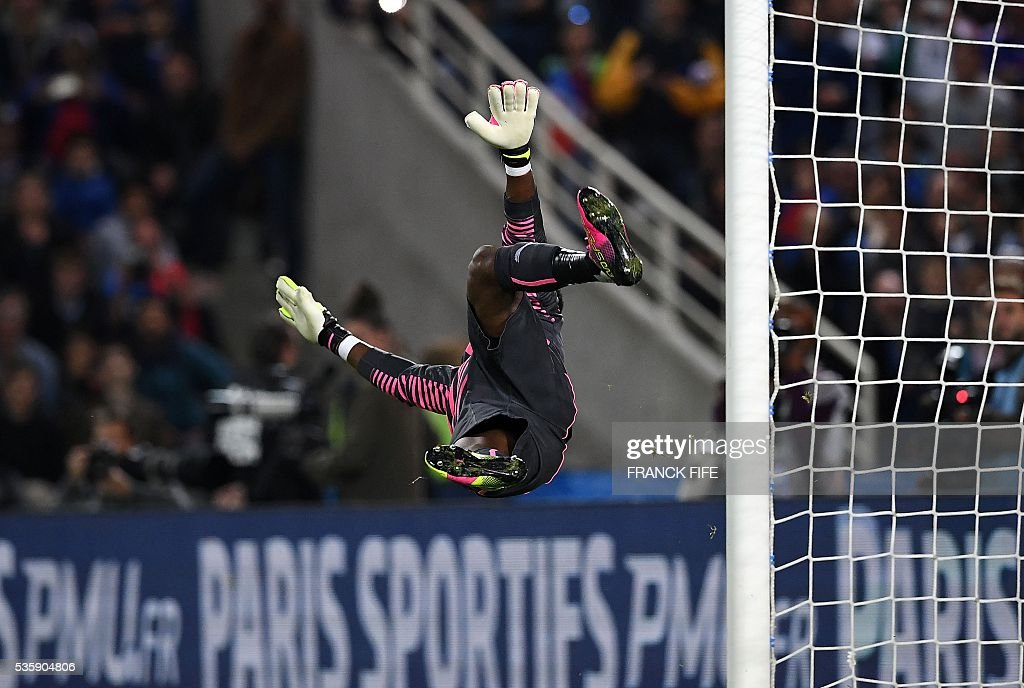 TOPSHOT - Cameroon's goalkeeper Fabrice Ondoa takes a goal of France's forward Dimitri Payet during the friendly football match between France and Cameroon, at the Beaujoire Stadium in Nantes, western France, on May 30, 2016. / AFP / FRANCK
