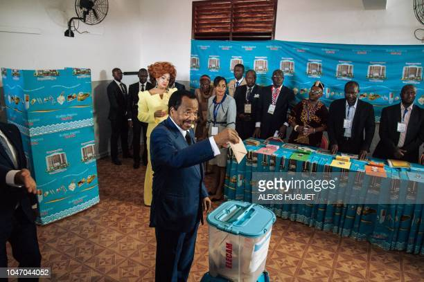 TOPSHOT Cameroon's incumbent President Paul Biya casts his ballot as his wife Chantal looks on in the polling station in Bastos neighbourhood in the...