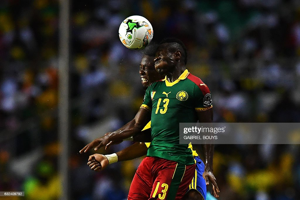 TOPSHOT - Cameroon's midfielder Christian Bassogog heads the ball with Gabon's defender Benjamin Ze Ondo (back) during the 2017 Africa Cup of Nations group A football match between Cameroon and Gabon at the Stade de l'Amitie Sino-Gabonaise in Libreville on January 22, 2017. / AFP / GABRIEL